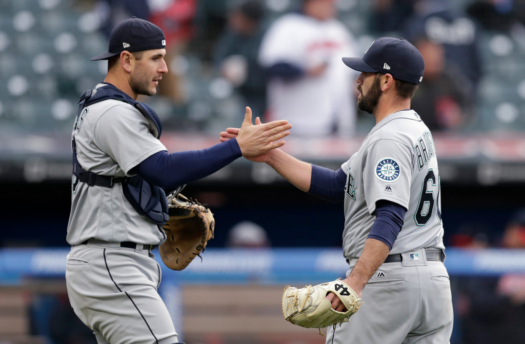 . Seattle Mariners relief pitcher Chasen Bradford, right, and catcher David Freitas celebrate after the Mariners defeated the Cleveland Indians 12-4 in a baseball game Saturday, April 28, 2018, in Cleveland. (AP Photo/Tony Dejak)