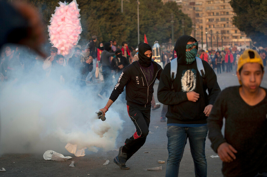 . An Egyptian protester runs with a teargas canister during clashes with riot police in downtown Cairo, Egypt, Saturday, March 9, 2013. Security officials say a protester has died during clashes between police and hundreds of stone-throwing demonstrators in central Cairo. The officials say the protester died Saturday on a Nile-side road where clashes have been taking place daily between anti-government protesters and police near two luxury hotels and the U.S. and British embassies. (AP Photo/Nasser Nasser)