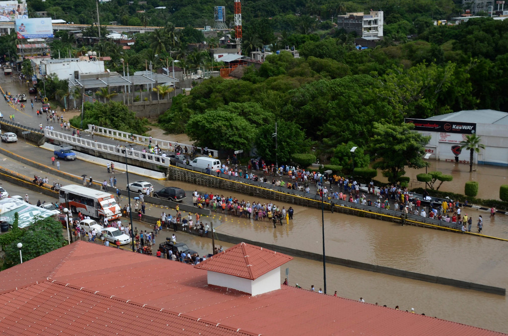 . People stand next to a flooded road in the city of Acapulco, Mexico, Tuesday Sept. 17, 2013. The death toll rose to 47 Tuesday from the unusual one-two punch of a tropical storm and a hurricane, hitting Mexico at nearly the same time. Authorities scrambled to get help into, and stranded tourists out of, the cutoff resort city. (AP Photo/Bernandino Hernandez)