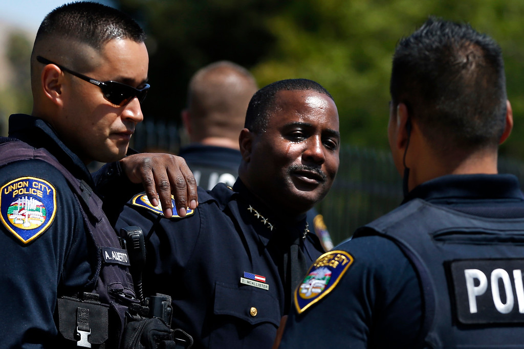 . Union City police Chief Darryl McAllister, center, is comforted by fellows officers after the police ceremonial procession of the body of Hayward police Sgt. Scott Lunger from the Coroner\'s Bureau in Oakland to Chapel of the Chimes Memorial Park in Hayward, Calif., on Thursday, July 23, 2015. McAllister worked for Hayward Police Department for 32 years where he knew Lunger, who was killed during a traffic stop in early Wednesday. (Ray Chavez/Bay Area News Group)