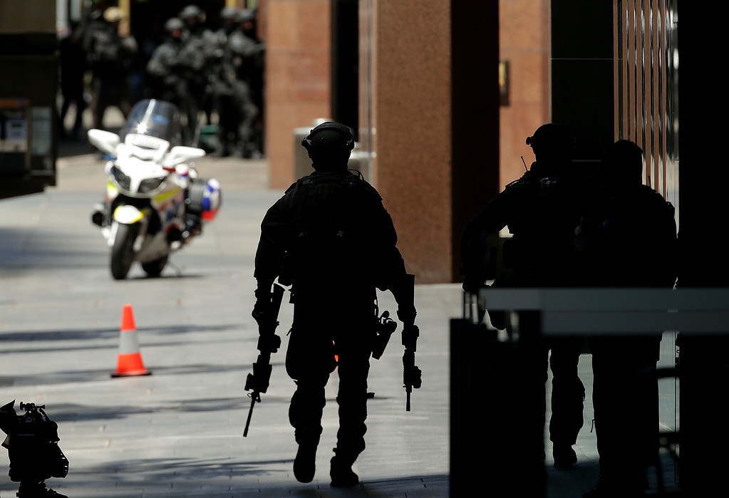 . SYDNEY, AUSTRALIA - DECEMBER 15:  An armed policeman is seen on Philip St walking towards Martin Place on December 15, 2014 in Sydney, Australia.  Police attend a hostage situation at Lindt Cafe in Martin Place.  (Photo by Mark Metcalfe/Getty Images)
