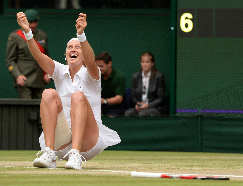 Description of . Petra Kvitova of Czech Republic celebrates defeating Eugenie Bouchard of Canada in their women's singles final at the All England Lawn Tennis Championships in Wimbledon, London, Saturday July 5, 2014. (AP Photo/Anthony Devlin. PA)