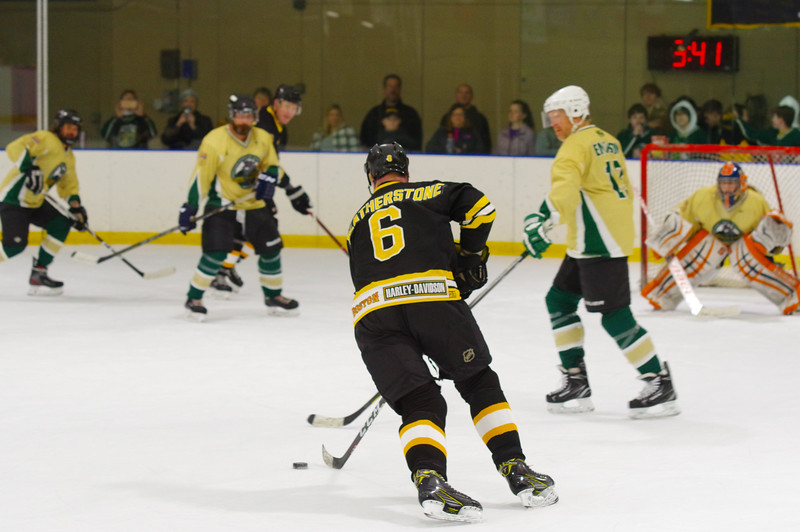 Bruins defenseman Glen Featherstone (6) enters the zone and wades into the NBYHL Alumni defense.