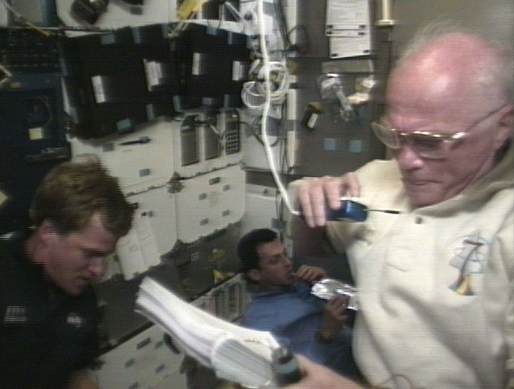 . U.S. Senator John Glenn, right, speaks to mission control during an experiment, while astronaut Scott Parazynski, left, helps and spanish astronaut Pedro Duque has a bite to eat aboard the Space Shuttle Discovery Saturday, Oct. 31, 1998, in this image from television. (AP Photo / NASATV)