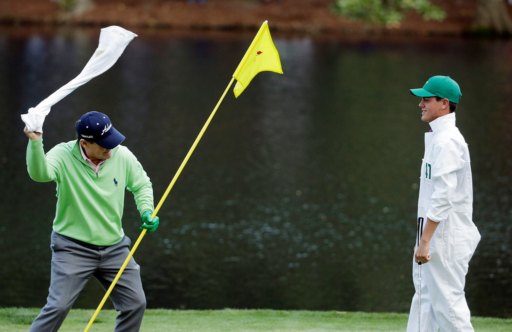 . Tom Watson whips his towel a Jarrod Jordan after Jordan putted on the ninth hole during the par three competition at the Masters golf tournament Wednesday, April 9, 2014, in Augusta, Ga. (AP Photo/Chris Carlson)