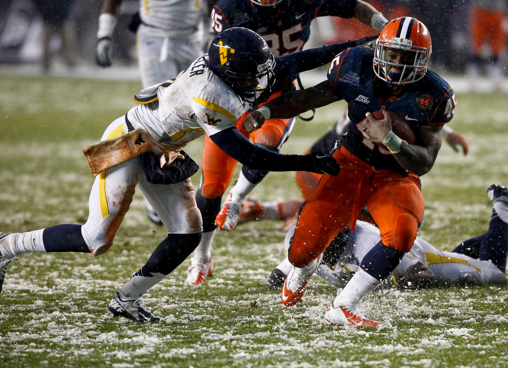 Description of . Jerome Smith #45 of the Syracuse Orange runs by Pat Miller #6 of the West Virginia Mountaineers during the New Era Pinstripe Bowl at Yankee Stadium on December 29, 2012 in the Bronx borough of New York City.  (Photo by Jeff Zelevansky/Getty Images)