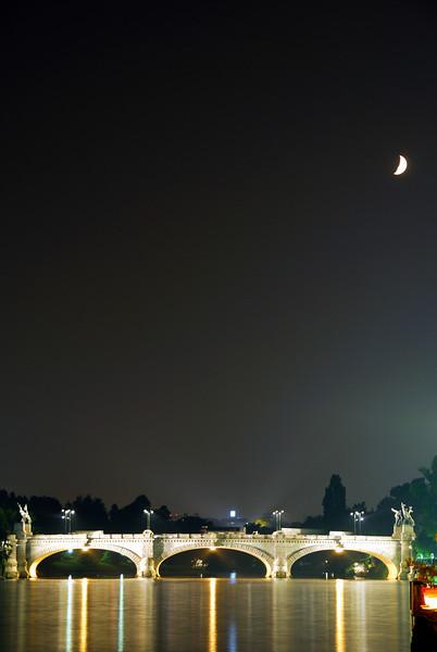 Crescent moon over a bridge in Turin