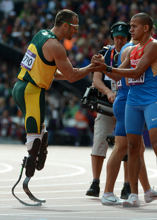 . South Africa\'s Oscar Pistorius, left, shakes hands with Russia\'s Maksim Dyldin after their Men\'s 400m heat at the Olympic Stadium for the London 2012 Olympics in London, England on Saturday, Aug. 4, 2012.  (Nhat V. Meyer/Mercury News)