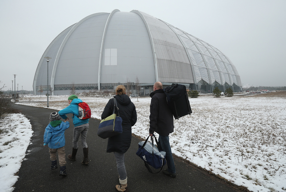 Description of . Visitors arrive at the giant hangar that houses the Tropical Islands indoor resort on February 15, 2013 in Krausnick, Germany. Located on the site of a former Soviet military air base, the resort occupies a hangar built originally to house airships designed to haul long-distance cargo. Tropical Islands opened to the public in 2004 and offers visitors a tropical getaway complete with exotic flora and fauna, a beach, lagoon, restaurants, water slide, evening shows, sauna, adventure park and overnights stays ranging from rudimentary to luxury. The hangar, which is 360 metres long, 210 metres wide and 107 metres high, is tall enough to enclose the Statue of Liberty.  (Photo by Sean Gallup/Getty Images)