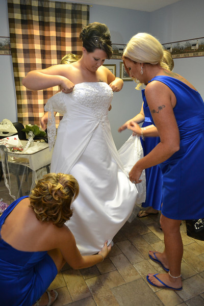 Bridesmaids helping to dress the bride.
