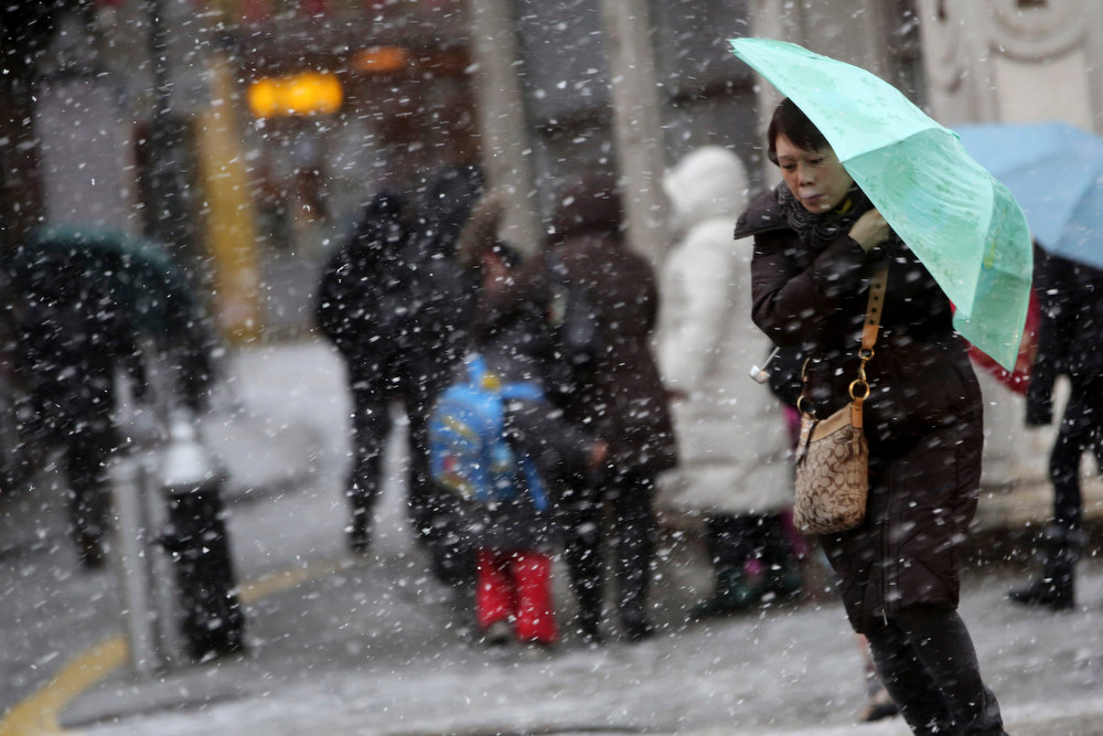 . A woman uses her umbrella to shield herself against the snow and wind while crossing the street in New York\'s Chinatown, Friday, Feb. 8, 2013. Snow began to fall as a massive blizzard headed for the American Northeast on Friday, sending residents scurrying to stock up on food and supplies ahead of a storm poised to dump up to 3 feet of snow from New York City to Boston and beyond. (AP Photo/Mary Altaffer)