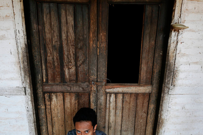 . Aung Myint Mo, a 22-year-old Muslim man, sits in front of a house damaged during recent violence in the town of Sit Kwin, some 150 km (93 miles) north of Yangon April 4, 2013. Officially, 43 people died in the recent anti-Muslim violence, which erupted in Meikhtila town in the centre of the country on March 20, 2013 and included the fire-bombing of mosques. It spread to at least 15 other towns and villages until President Thein Sein ordered soldiers and police to crack down.  REUTERS/Damir Sagolj
