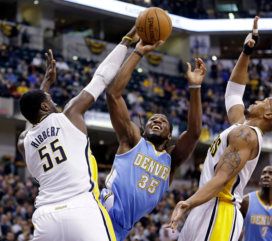 . Denver Nuggets forward Kenneth Faried (35) shoots between Indiana Pacers center Roy Hibbert (55) and David West in the first half of an NBA basketball game in Indianapolis, Monday, Feb. 10, 2014. (AP Photo/Michael Conroy)