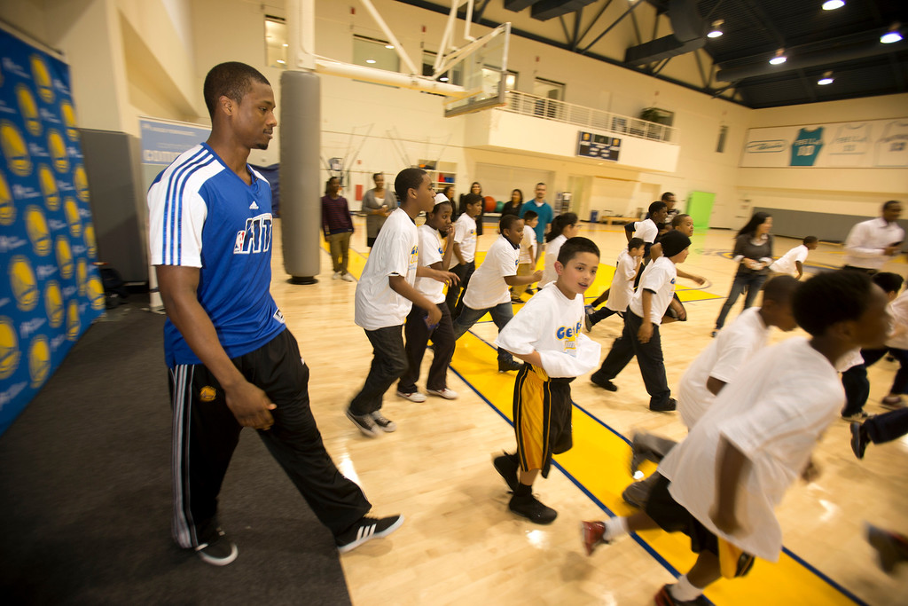 . Golden State Warriors forward Harrison Barnes, left, walks on to the court with a group of children participating in a basketball clinic at the Warriors practice facility in downtown Oakland, Calif., Wednesday, Jan. 30, 2013. The Warriors and Kaiser Permanente hosted the event as part of the NBA FIT Live Healthy Week. (D. Ross Cameron/Staff)