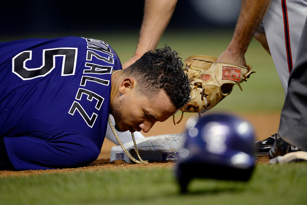 . Carlos Gonzalez (5) of the Colorado Rockies lays at third base after failing to make a clean slide safely and hurting himself in the process at Coors Field. Major League Baseball action between the Colorado Rockies and the Washington Nationals on Monday, July 21, 2014. (Photo by AAron Ontiveroz/The Denver Post)