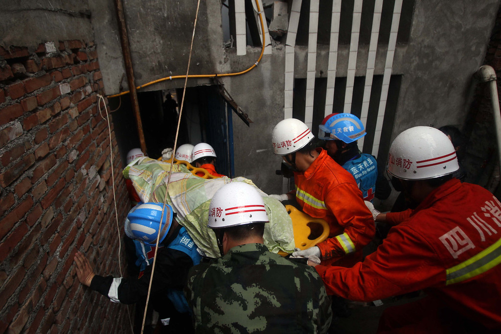 . LUSHAN, CHINA - APRIL 23:  (CHINA OUT) Rescuers carry a victim\'s body out of a damaged building on April 23, 2013 in Lushan County, China. A powerful earthquake struck the steep hills of China\'s southwestern Sichuan province on the morning of April 20, leaving at least 193 people dead and more than 12,200 injured.  (Photo by ChinaFotoPress/Getty Images)