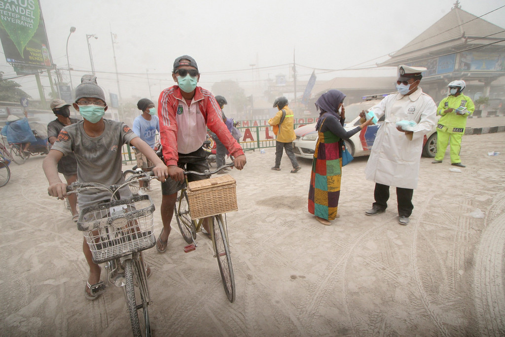 . An Indonesian police officer distributes masks at a road covered with ash from the Mount Kelud volcano in Yogyakarta, Indonesia, 14 February 2014.   EPA/BIMO SATRIO