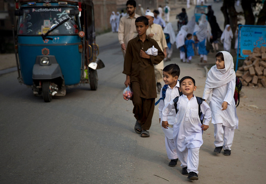 . Pakistani children on their way to school in Mingora, Swat Valley, Pakistan on Saturday, Oct. 5, 2013. A year ago Pakistani girl Malala Yousufzai was shot in the head by a Taliban attacker in Mingora on her way home from school.  Malala remains in Britain and her assailant is still at large, police say the case is closed. Many Pakistanis publicly wonder whether the shooting was staged to create a hero for the West to embrace. (AP Photo/Anja Niedringhaus)