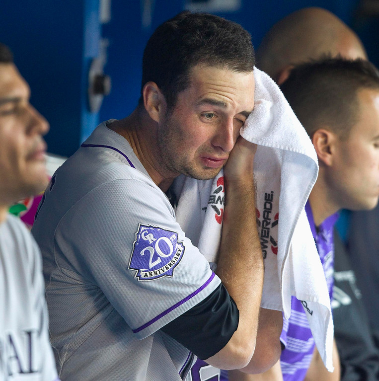 . Colorado Rockies starting pitcher Jeff Francis sits in the dugout after giving up four runs in the first inning to the Toronto Blue Jays in their MLB Interleague baseball game in Toronto June 18, 2013. REUTERS/Fred Thornhill