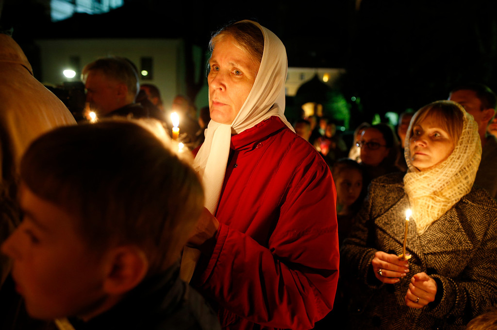 . Lithuanian Orthodox believers hold candles during an Easter vigil mass in the Prechistensky, the Cathedral Palace, in Vilnius, Lithuania, Saturday, April 19, 2014. (AP Photo/Mindaugas Kulbis)
