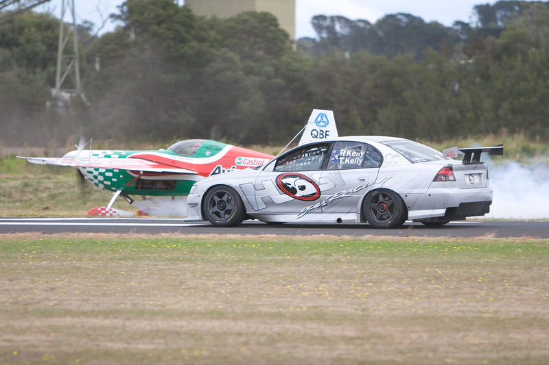 """Pip Borrman's Castrol Aviator Edge 540 momentarily out-dragged Todd Kelly's V8 Supercar """"thrill ride"""" Commodore. The car beat the aircraft in the first match race but Borrman challenged the Bathurst 1000 winner to a second duel and justice was done!  When Todd had to brake at the end of runway 17, Pip flung the Edge 540 skywards. A thumb-the-nose sort of gesture... """"You might have beaten me to the end of the strip but look what I can do."""""""