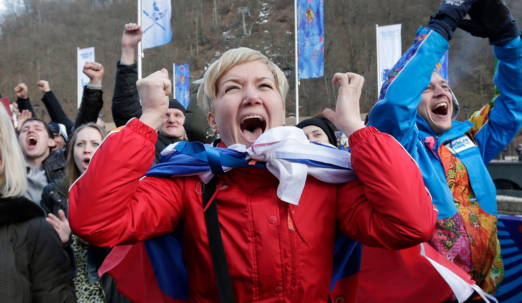. Evlampieva Valentinovna celebrates with Russian fans following a goal by Russia\'s Pavel Datsyuk during the second period of a men\'s ice hockey game against the United States during the 2014 Winter Olympics, Saturday, Feb. 15, 2014, in Krasnaya Polyana, Russia. (AP Photo/Charles Krupa)