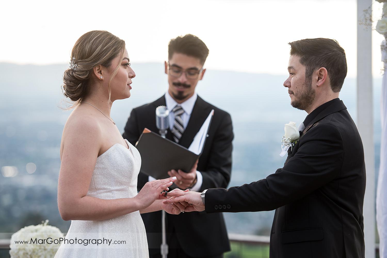 bride putting wedding ring on groom's finger at Mt Hamilton GrandView Restaurant in San Jose