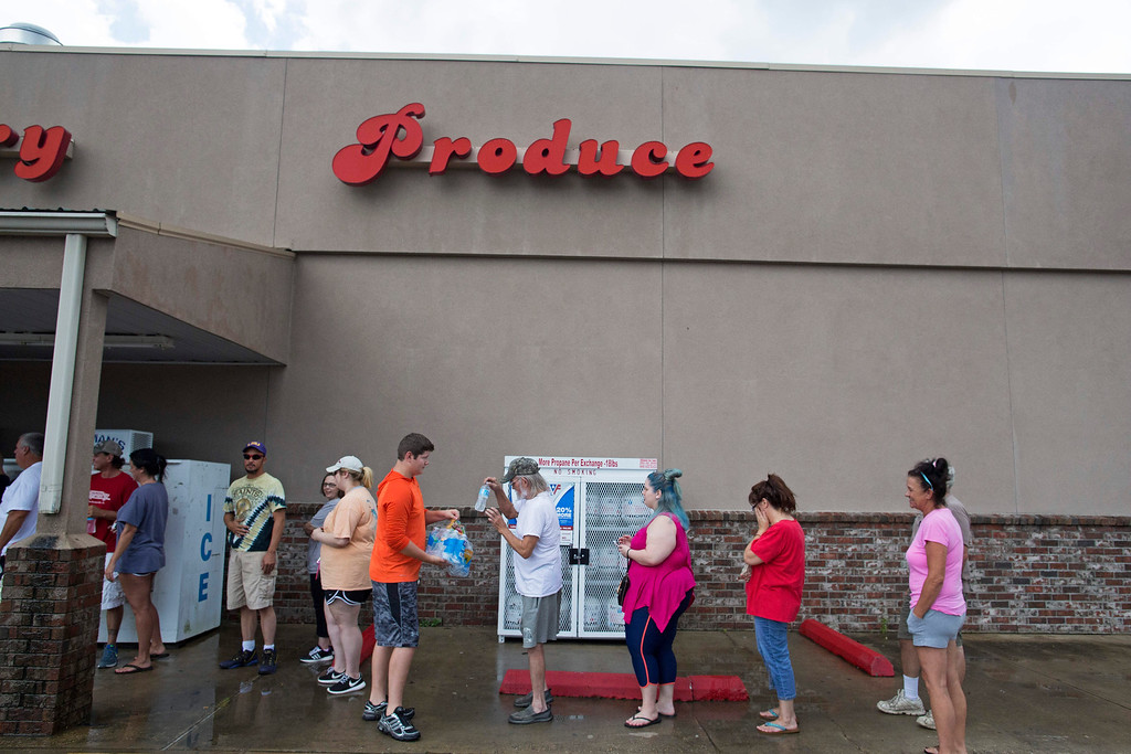 . Eli Turnage, 14, center, hands out water to people waiting in line at the Carter\'s Supermarket in Livingston, La., as flood water starts to subside in the region, Monday, Aug. 15, 2016. The store opened for the first time today since flooding started in the region. (AP Photo/Max Becherer)