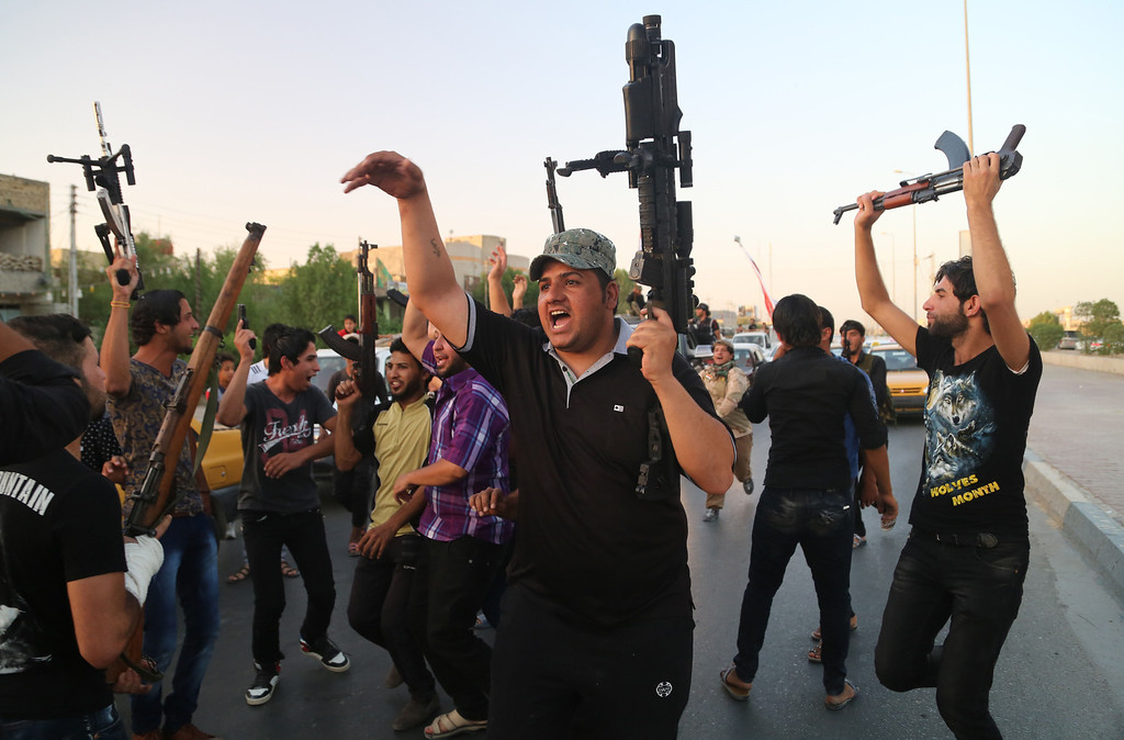 . Shiite tribal fighters raise their weapons and chant slogans against the al-Qaida-inspired Islamic State of Iraq and the Levant (ISIL) in Basra, Iraq\'s second-largest city, 340 miles (550 kilometers) southeast of Baghdad, Iraq, Sunday, June 15, 2014. Emboldened by a call to arms by the top Shiite cleric, Iranian-backed militias have moved quickly to the center of Iraqís political landscape, spearheading what its Shiite majority sees as a fight for survival against Sunni militants who control of large swaths of territory north of Baghdad. (AP Photo/ Nabil Al-Jurani)