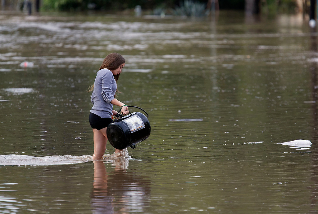 . Alexis Wiesman, 14, helps to retrieve some belongings that were washed away in the flood water from her grandparents home in Austin, Texas, on Thursday, Oct. 31, 2013. Heavy overnight rains brought flooding to the area. (AP Photo/Austin American-Statesman, Ralph Barrera)