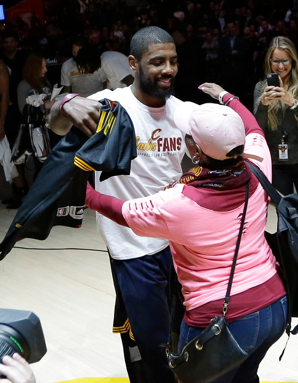 . Cleveland Cavaliers\' Kyrie Irving hugs a fan before giving her his jersey for Fan Appreciation night after an NBA basketball game between the Toronto Raptors and the Cleveland Cavaliers, Wednesday, April 12, 2017, in Cleveland. (AP Photo/Tony Dejak)