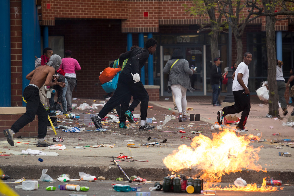 . BALTIMORE, MD - APRIL 27:  People carrying goods leave a CVS pharmacy near the intersection of Pennsylvania Avenue and North Avenue , April 27, 2015 in Baltimore, Maryland. Riots have erupted in Baltimore following the funeral service for Freddie Gray, who died last week while in Baltimore Police custody. (Photo by Drew Angerer/Getty Images)