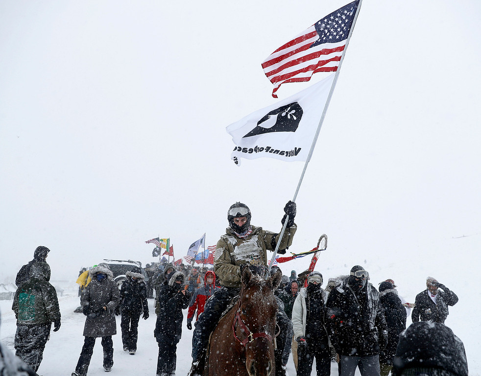 . U.S. Navy veteran Kash Jackson rides a horse during a march with fellow veterans and Native American to a closed bridge outside the Oceti Sakowin camp where people have gathered to protest the Dakota Access oil pipeline in Cannon Ball, N.D., Monday, Dec. 5, 2016. (AP Photo/David Goldman)