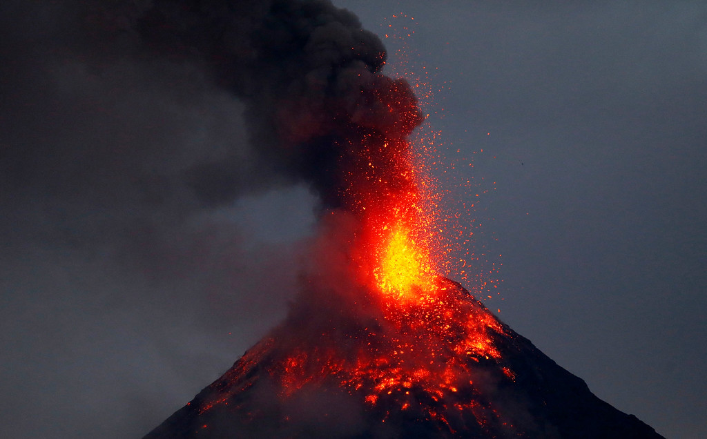 . Mayon volcano spews red-hot lava in another eruption as seen from Legazpi city, Albay province, roughly 200 miles (340 kilometers) southeast of Manila, Philippines, Tuesday, Jan. 23, 2018. Mayon has spewed fountains of red-hot lava and massive ash plumes anew in a dazzling but increasingly dangerous eruption that has sent 56,000 villagers fleeing to evacuation centers. (AP Photo/Bullit Marquez)