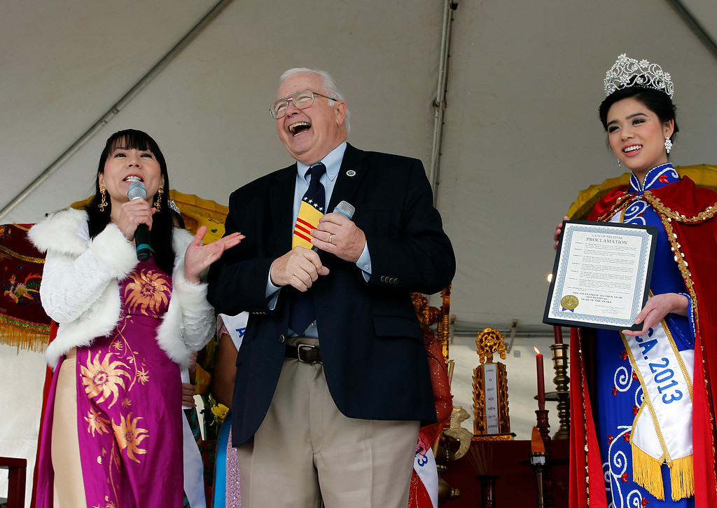. At center, Pete McHugh, former Mayor of Milpitas laughs at being called Santa Claus by Queenie Huyen-Tran, producer of the Miss Vietnam of Northern California Pageant, left, at the Tet festival hosted by the Coalition of Nationalist Vietnamese Organizations of Northern California (CONVONCA) at the Santa Clara County Fairgrounds in San Jose, Calif. on Saturday, February 2, 2013.  At right is Tranle Nguyen Minh, Miss Vietnam of Northern California 2013.  (LiPo Ching/Staff)