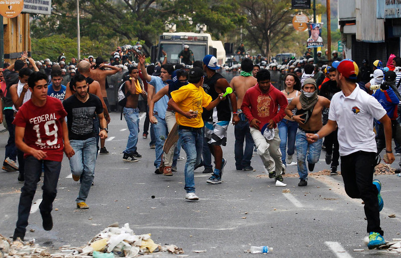 . Supporters of opposition leader Henrique Capriles run from riot police as they demonstrate for a recount of the votes in Sunday\'s election, in Caracas, April 15, 2013. Capriles called on Venezuelans to take to the streets and peacefully demand a vote recount if election authorities formally proclaim Hugo Chavez\'s chosen successor, Nicolas Maduro, as the next president.  REUTERS/Tomas Bravo