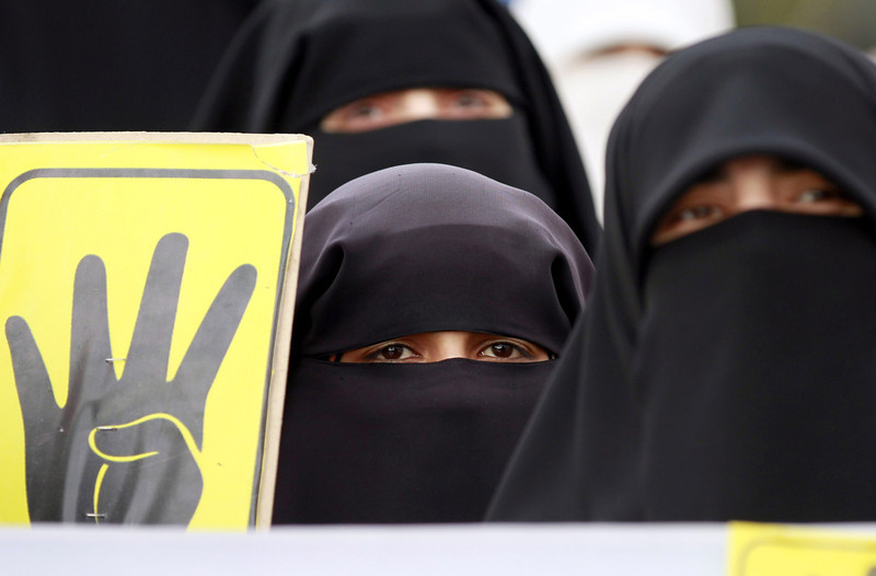 ". A fully-veiled woman holds a sign bearing a four finger symbol known as ""Rabaa\"", meaning four in Arabic, which is associated with those killed in the crackdown on the Rabaa al-Adawiya protest camp in Cairo last year as they protest in solidarity with Egyptians on the third anniversary of the 2011 revolt that toppled Egypt\'s former president Hosni Mubarak outside the Egyptian embassy in Amman on January 25, 2014. Mubarak was forced to step down on February 11, 2011 after 18 days of demonstrations that left some 850 people dead, ending his three-decade rule of the Arab world\'s most populous country. (KHALIL MAZRAAWI/AFP/Getty Images)"