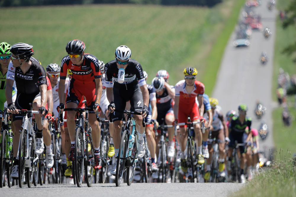 . One rider holds a drinking bottle with his teeth as the rest of the pack blurs in the heat haze during the twelfth stage of the Tour de France cycling race over 185.5 kilometers (115.3 miles) with start in Bourg-en-Bresse and finish in Saint-Etienne, France, Thursday, July 17, 2014. (AP Photo/Laurent Cipriani)