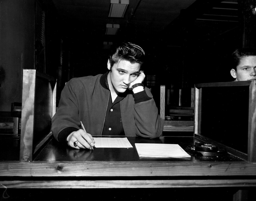 . Singer Elvis Presley, 21, takes his pre-induction written examination as he is processed for the U.S. Army in Memphis, Tenn., Jan. 4, 1957.  (AP Photo)
