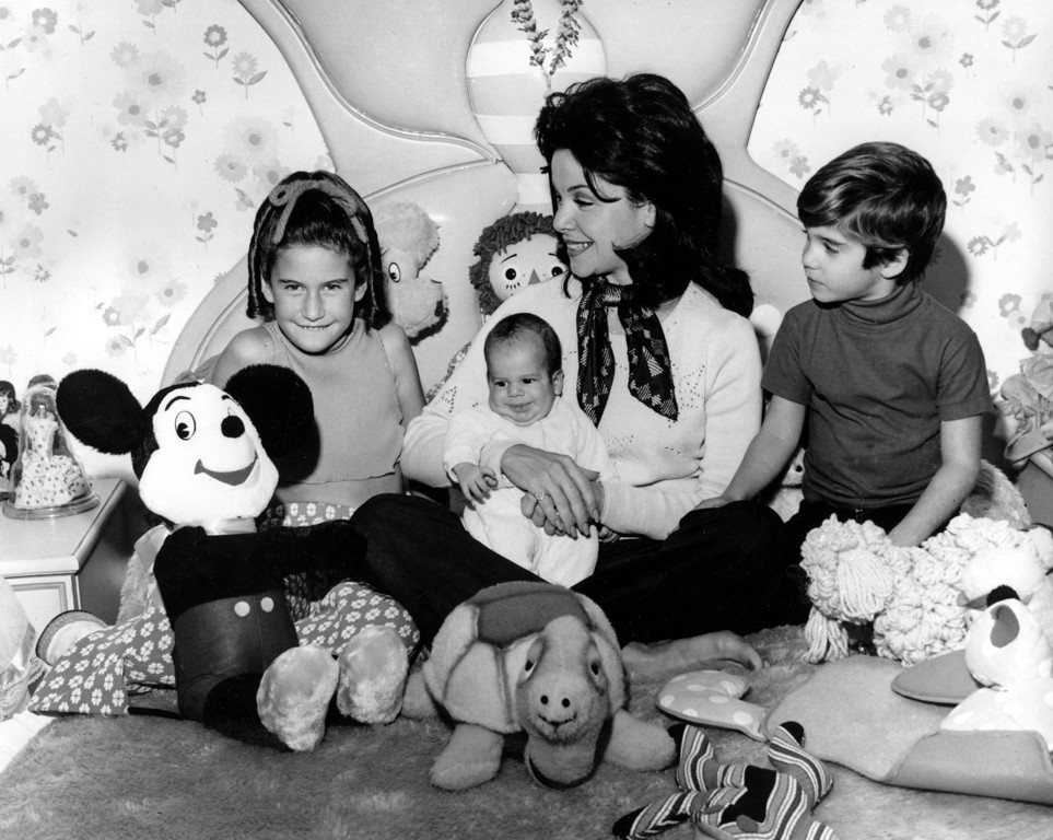 . Actress and former Mouseketeer Annette Funicello holds her infant son, 7-month-old Jason, while watching a revival TV show of the old Mickey Mouse Club series with 9-year-old daughter Gina, and 5-year-old son Jack Jr., at her home in Burbank, Calif., on March 11, 1975. (AP Photo)