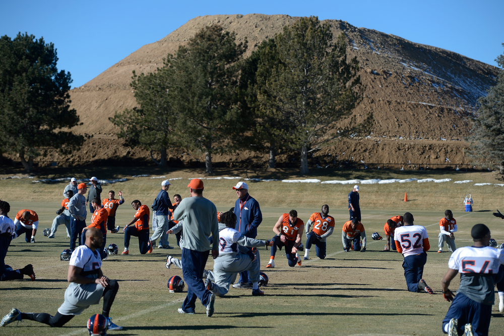 . The Denver Broncos begin their practice at Dove Valley Saturday morning, January 25, 2014. The large dirt hill in the background was excavated from the Broncos new indoor practice facility under construction, scheduled to open in November 2014. (Photo By Andy Cross / The Denver Post)