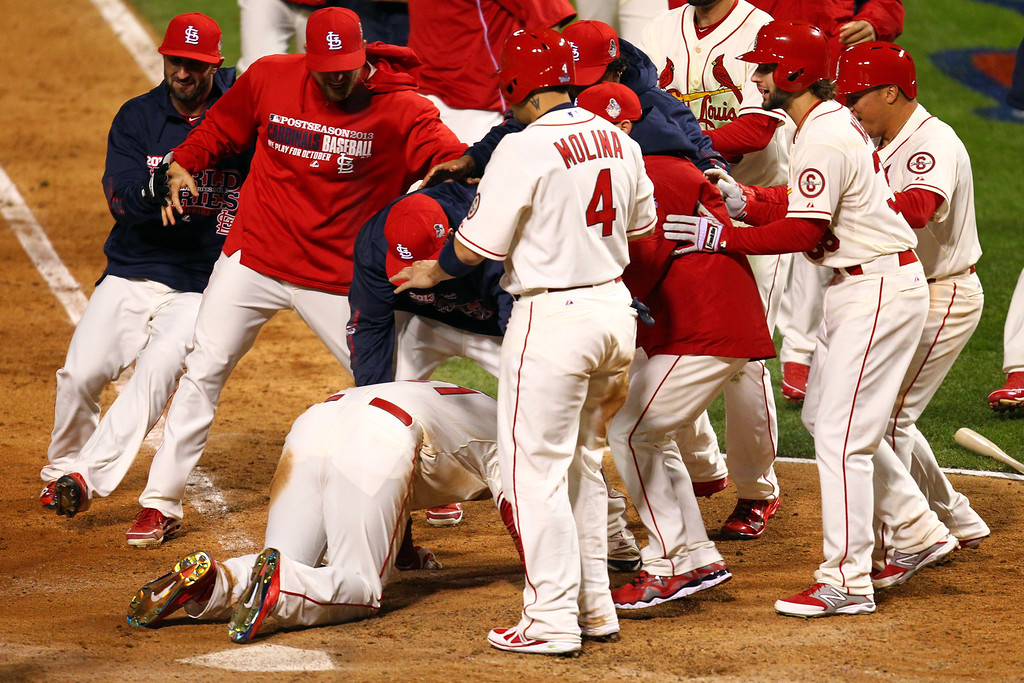 . ST LOUIS, MO - OCTOBER 26:  The St. Louis Cardinals surround Allen Craig #21 after he scored the winning run against the Boston Red Sox in the ninth inning during Game Three of the 2013 World Series at Busch Stadium on October 26, 2013 in St Louis, Missouri.  (Photo by Dilip Vishwanat/Getty Images)