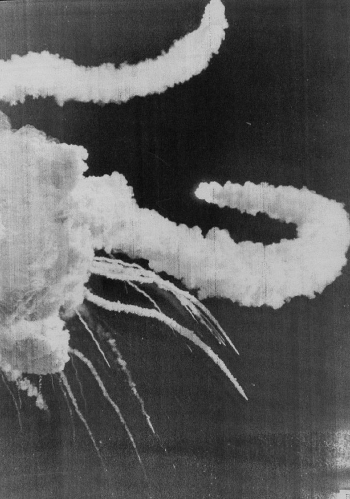 Description of . Two solid rocket boosters twist away from the explosion of space shuttle Challenger on Jan. 28, 1986.  Debris from the orbiter falls to the ground. Denver Post Library Archive