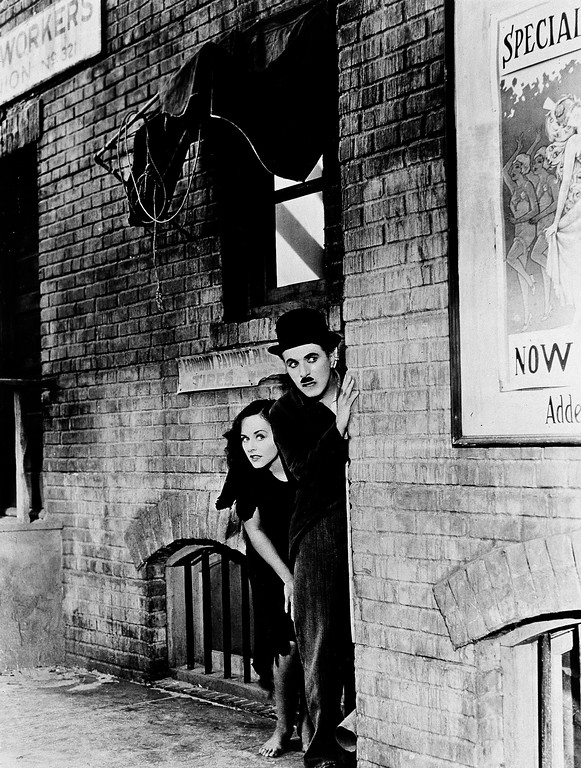 ". Actors Charlie Chaplin and Paulette Goddard strike familiar poses from a past film ""The Kid"", during the filming of ""Modern Times,"" 1936.  (AP Photo)"
