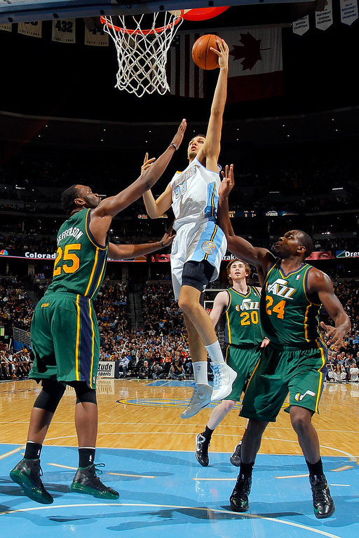 . Evan Fournier #94 of the Denver Nuggets lays up a shot between Al Jefferson #25 and Paul Millsap #24 of the Utah Jazz at the Pepsi Center on January 5, 2013 in Denver, Colorado. The Nuggets defeated the Jazz 110-91. (Photo by Doug Pensinger/Getty Images)