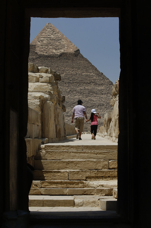 . Tourists walk in front of Khafre pyramid, background, at the historical site of the Giza Pyramids, background, near Cairo, Egypt, Tuesday, Aug. 27, 2013.  The chairman of the Egyptian Airports Co. says some flights are arriving nearly empty to Egypt and that passenger traffic in the past week has fallen by half. Due to the country\'s violent turmoil, some flights that can carry more than 100 passengers from Europe arrive with just nine and return full from beach resorts. (AP Photo/Lefteris Pitarakis)