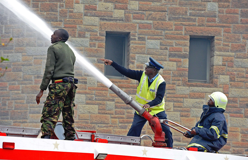 . Firefighters shoot a water canon to control a blaze outside the burning Jomo Kenyatta International airport in Nairobi on August 7, 2013. A massive fire shut down Nairobi\'s international airport today with flights diverted to regional cities as firefighters battled to put out the blaze in east Africa\'s biggest transport hub. AFP PHOTO/StringerSTRINGER/AFP/Getty Images