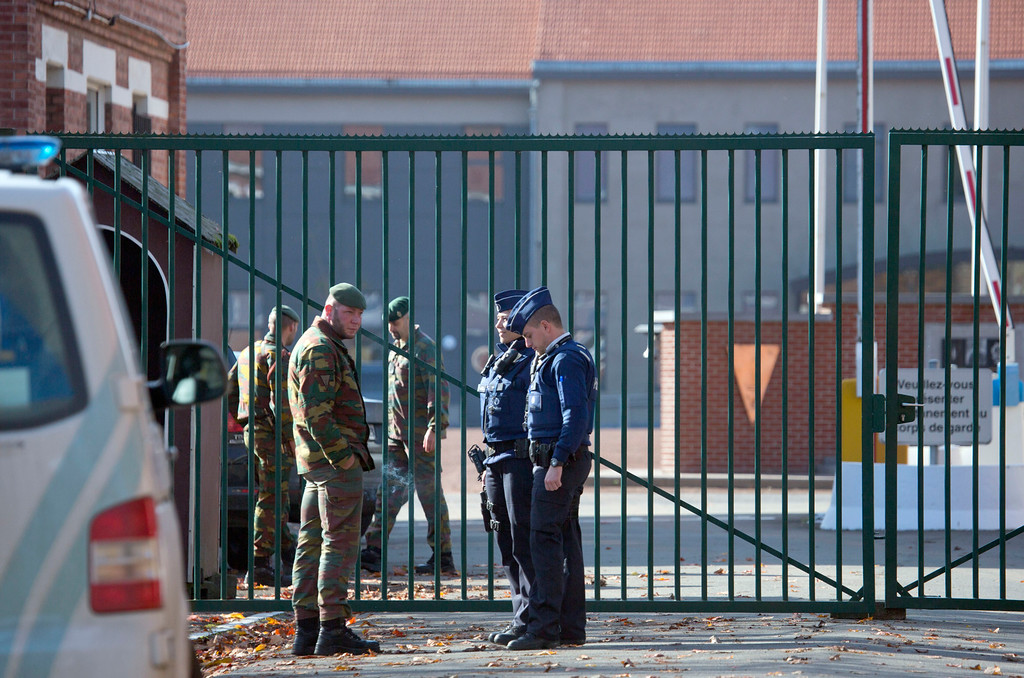 . Police and military personnel stand outside a military barracks in Flawinne, Belgium on Monday, Oct. 26, 2015. Belgian media are reporting a car has attempted to crash through the gates of an army barracks and that shots have been fired. (AP Photo/Virginia Mayo)