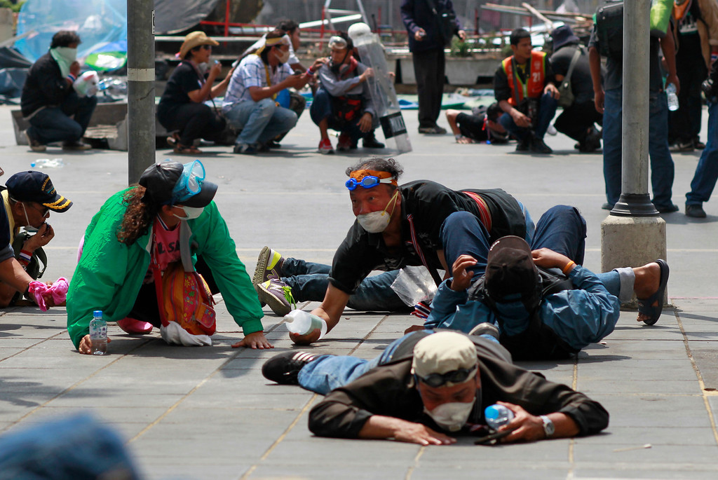 . Anti-government protesters crawl on the ground as they come under fire from riot police during clashes in Bangkok, Thailand, Tuesday, Feb. 18, 2014. (AP Photo/Wally Santana)