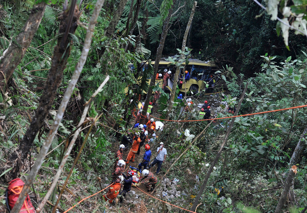 . Malaysian emergency services personnel rescue a passenger, seen bottom on a stretcher, after a passenger bus carrying tourists and local residents fell into a ravine near the Genting Highlands, about an hour\'s drive from Kuala Lumpur, Malaysia, Wednesday, Aug. 21, 2013. (AP Photo)